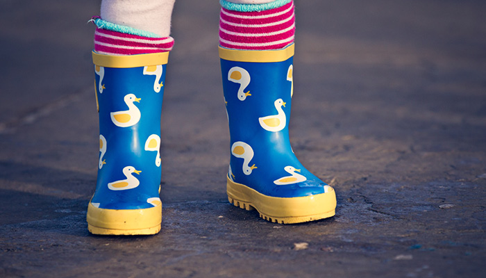 Close up of a childs feet wearing colourful wellies with ducks on them.