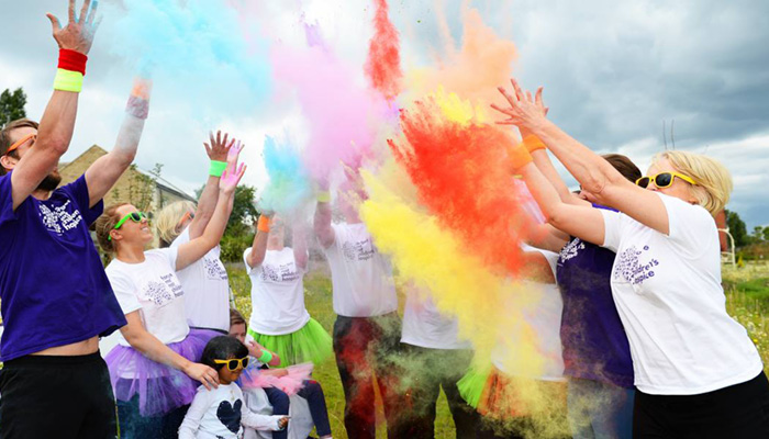 charity event showing people throwing coloured powder over themselves for the Colour Run event.