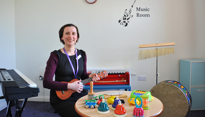 woman playing child's guitar with children's toys on table next to her.